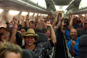 Customers on a relief flight celebrate after they were told they would all get free cheeseburgers.