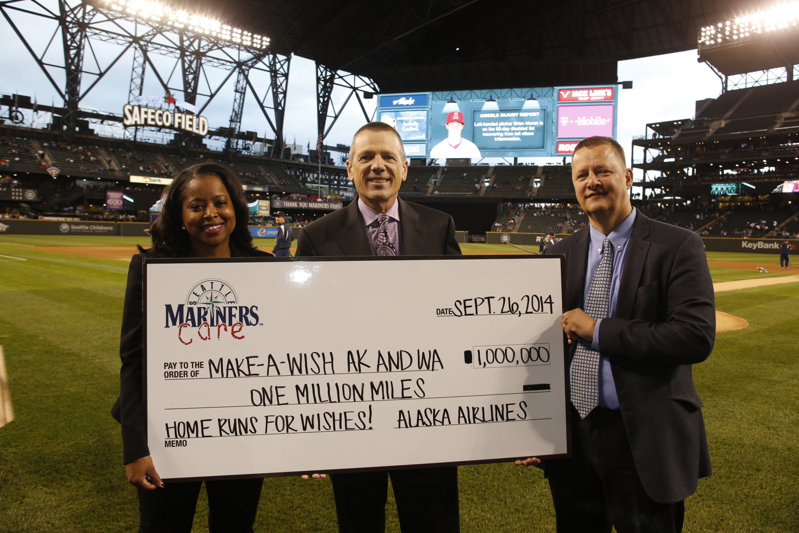 Alaska Airlines' Shaunta Hyde presents 1 million miles to Barry McConnell, Make-a-Wish Alaska and Washington chapter president and CEO, and Make-A-Wish board chair Mitch Hansen before a Mariners game on Friday, Sept. 26.