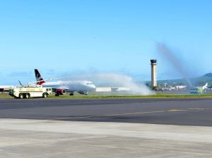 Photo of a Virgin America plane arriving in Maui for the first time under a water arc.