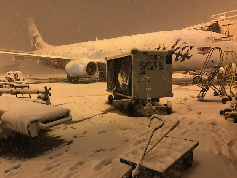 Snow covers Alaska Airlines plane