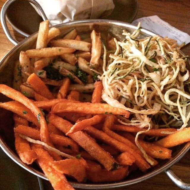 Photo of sweet potato fries in a bowl mixed with regular fries, zucchini and onion.