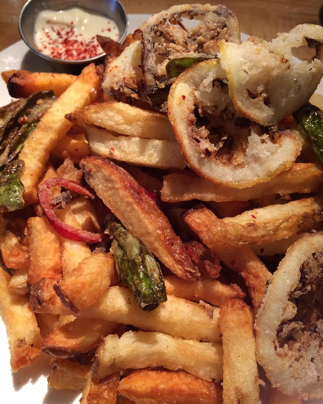 Photo of french fries mixed with lemons and chilis.