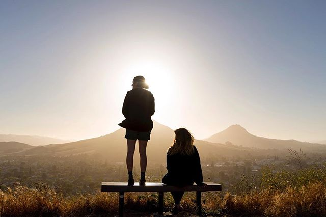 A photo of two hikers on top of Terrace Hill watching the sunset in SLO.,