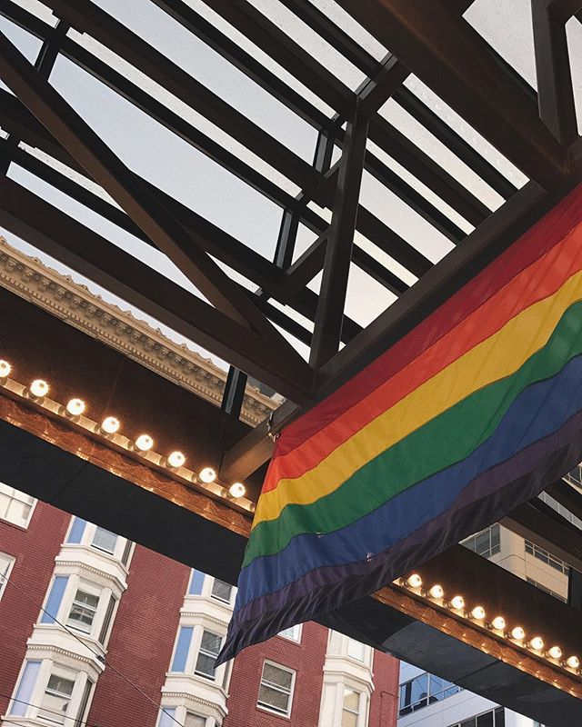 This is a photo of a rainbow flag hanging from a rooftop in San Francisco.