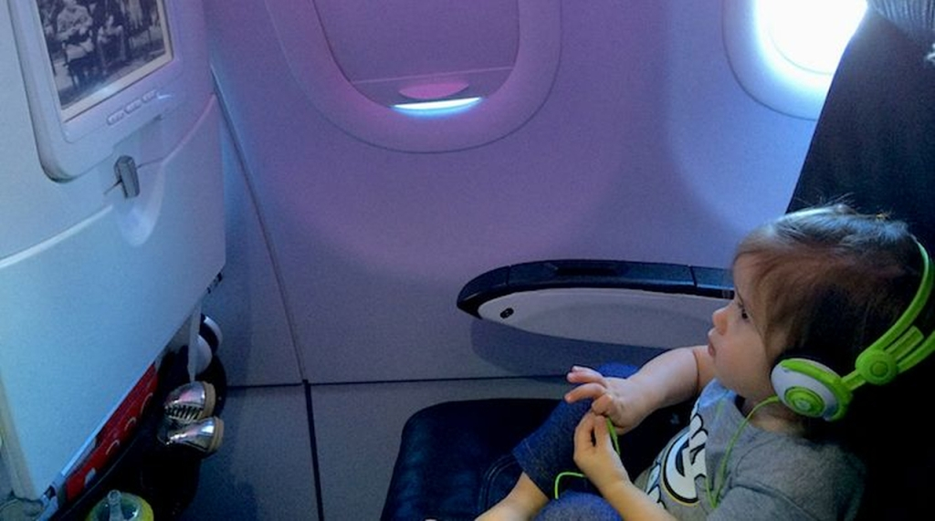 This is a photo of a child watching a movie on an airplane.