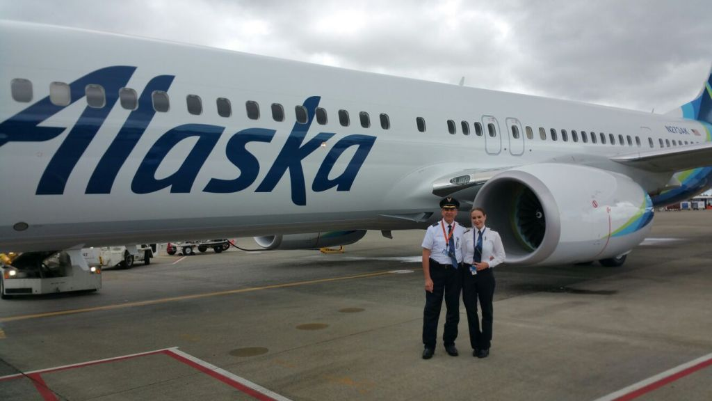 This is a photo of a father-daughter pilot team in front of an Alaska Airlines jet