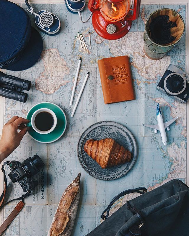 Photo of coffee, camera, baked goods, travel journals, headphones, travel bag, lantern, matches and mini airplanes over a map of the world.