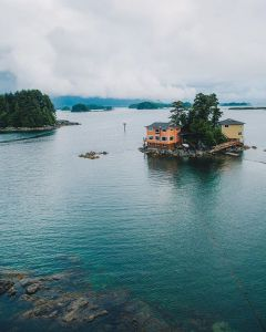 Photo from above of small island with two houses on it.
