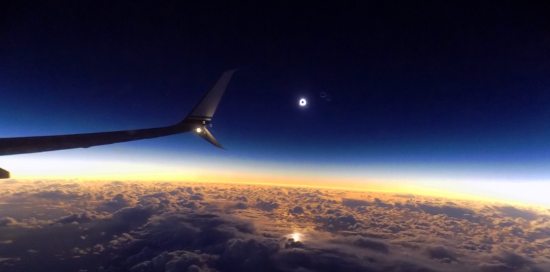 This is a photo of an Alaska Airlines winglet, taken while flying above the clouds. A total solar eclipse is happening in the distance.