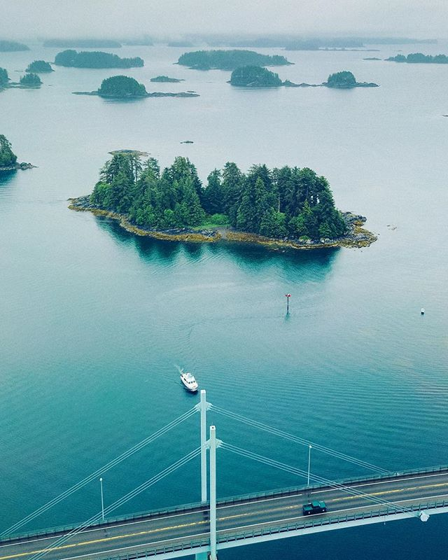 Photo from up above a bridge, with a boat and island in the water in the background.