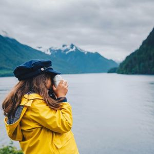 Photo of a girl standing on the shore taking photos of mountains in the distance.