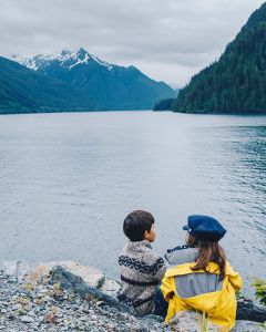 Photo of two children sitting on the shore with a view of mountains in the background.