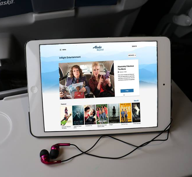 This is a photo of an Apple iPad sitting on an aircraft tray table using the Alaska