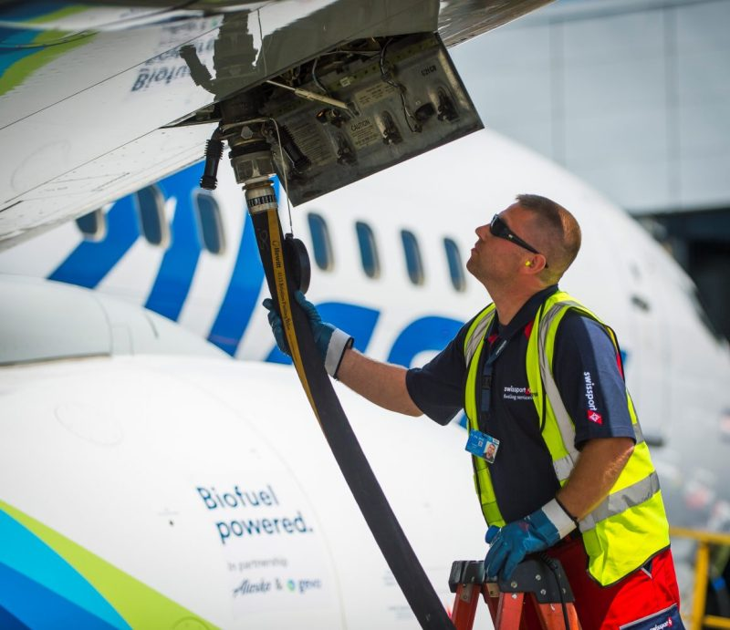 A photo of a male Swissport employee fueling an Alaska Airlines jet with biofuel.