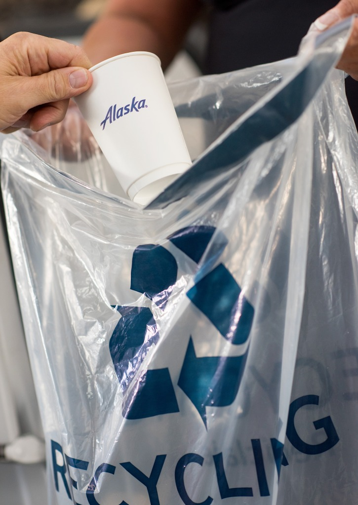 A photo of a customer throwing an Alaska coffee cup in a recycling bag held by an Alaska Airlines flight attendant onboard an Alaska Airlines aircraft.