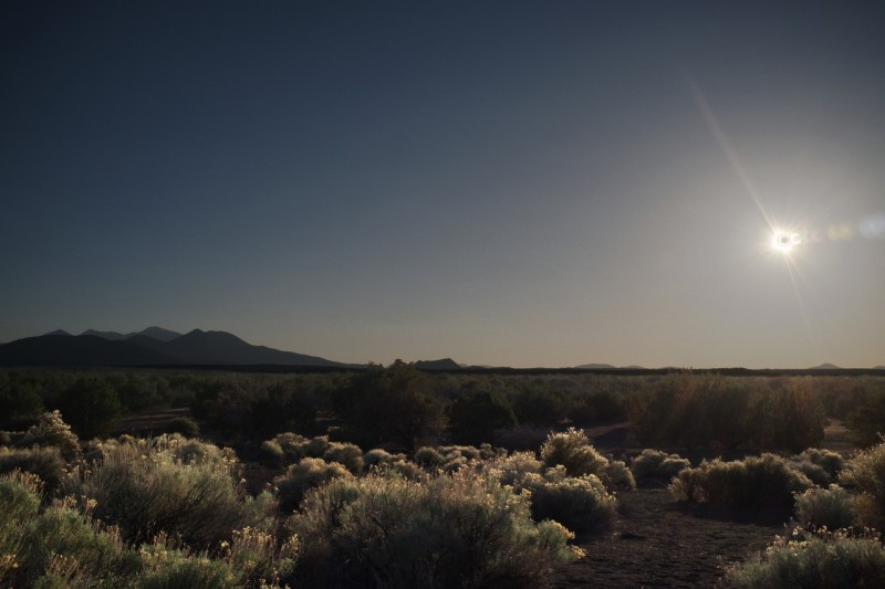 A photo looking out over the Arizona dessert with a partial solar eclipse shining in the sky.