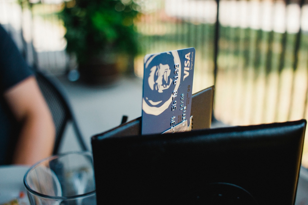 A photo of an Alaska Airlines Visa Signature card sticking out of a billfold on a restaurant table.
