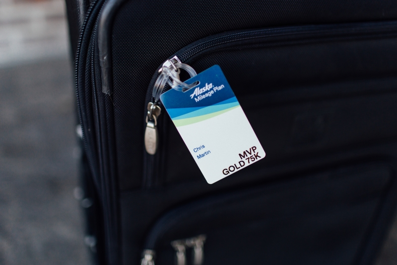 Photo of an Alaska Airlines MVP Gold 75K luggage tag on a black roller bag suitcase.