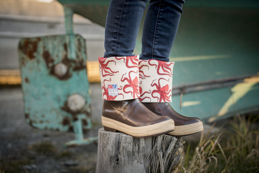 Photo of person wearing brown XTRATUF boots with the tops rolled down, featuring a red Octopus Salmon Sisters design. Person is standing on top of tree stump in front of an old, grounded fishing boat