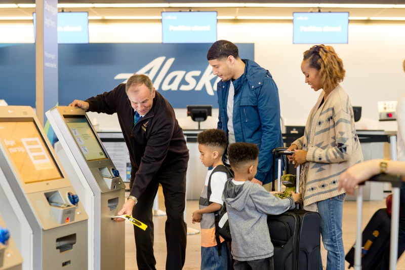 A photo of a male Alaska Airlines agent helping print bag tags at a Self-Tag station for a family of 4 traveling together.