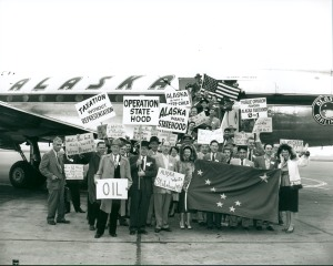 A group of Alaskans standing outside an Alaska Airlines DC-4 jet holding signs advocating for statehood and an Alaska state flag.