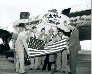 A photo of a group of men standing outside of an Alaska Airlines DC-4 aircraft with a 48-star American flag. One man in the middle is placing a 49th star on the flag.