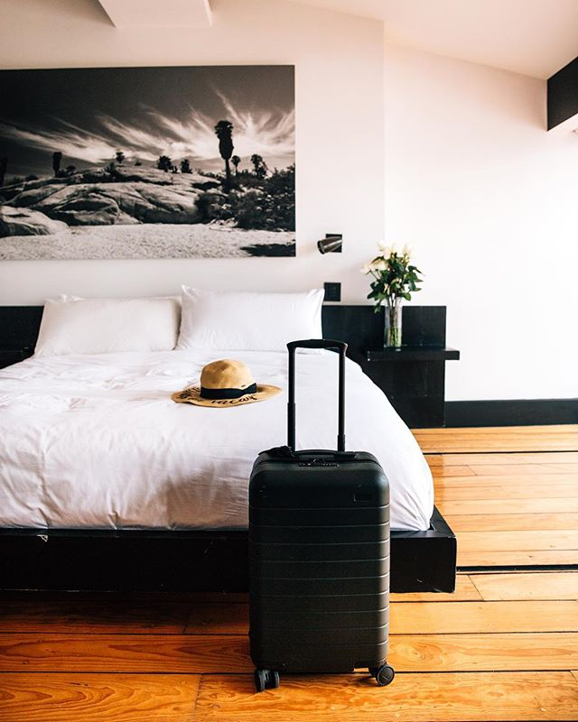 This is a photo of a hotel room with wood floors, a large bed, a suitcase and a hat sitting on the bed.