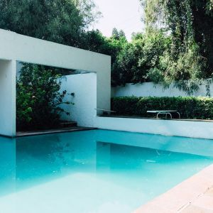 This is a photo of a swimming pool, featuring white block-like architecture surrounding it.