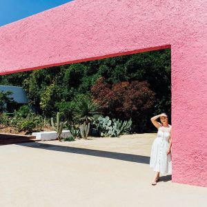 This is a photo of a girl standing under a large pink block-like architectural structure.