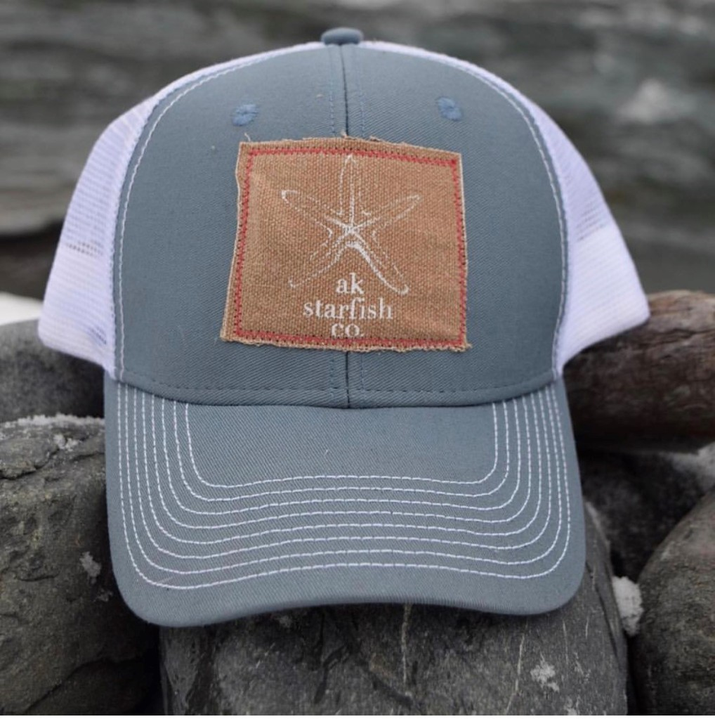 This is a photo of a trucker hat sitting on rocks on a beach. The hat features a Carhartt material patch with the akstarfish co flagship design.
