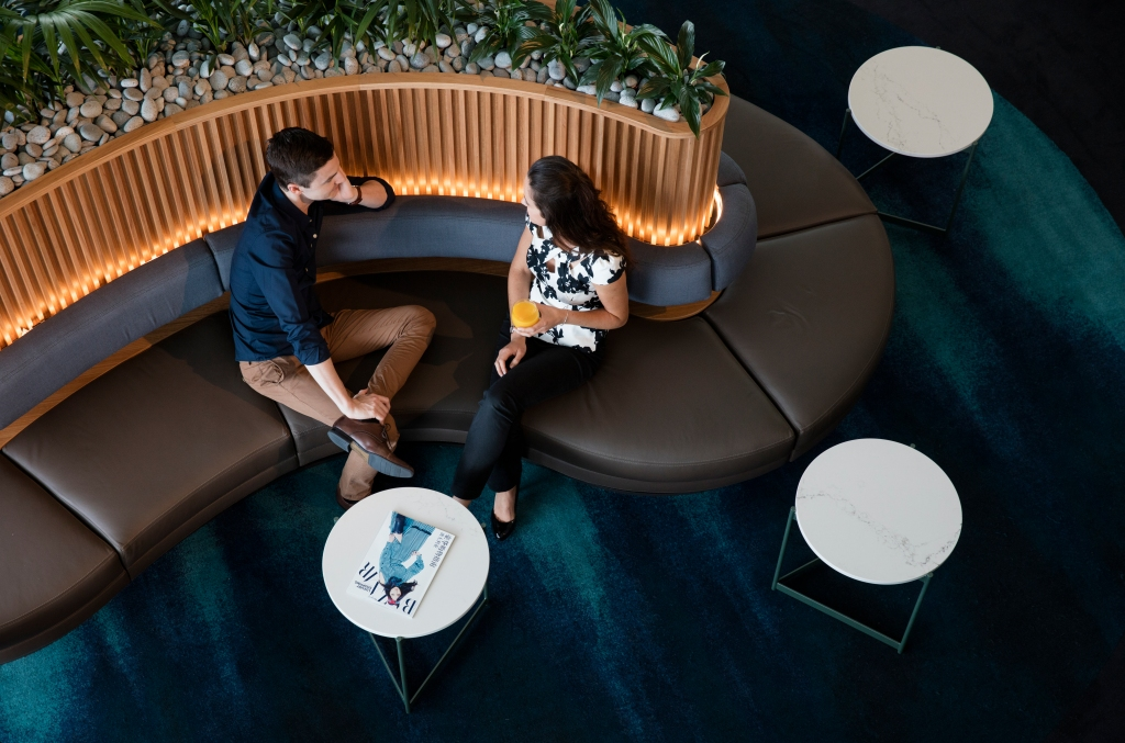 This is a photo of two travelers sitting on a bench in the Qantas lounge.