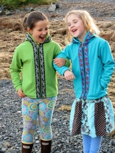 This is a photo of two young girls walking arm in arm on a beach. The girl on the left is wearing a green softshell jacket and the girl on the right is wearing a blue softshell jacket.