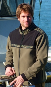 This is a photo of a man wearing a brown jacket with an Alaska Native trim , while on a fishing boat.