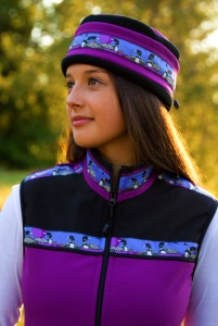 This is a photo of a woman wearing a purple Copper River Fleece vest and matching hat with a songbird trip