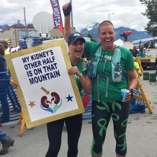 "This is a photo of Jenny Stansel holding a sign that says ""My Kidney's Other Half is on that Mountain!"" while standing next to Jodi Harskamp at the finish line of a race."