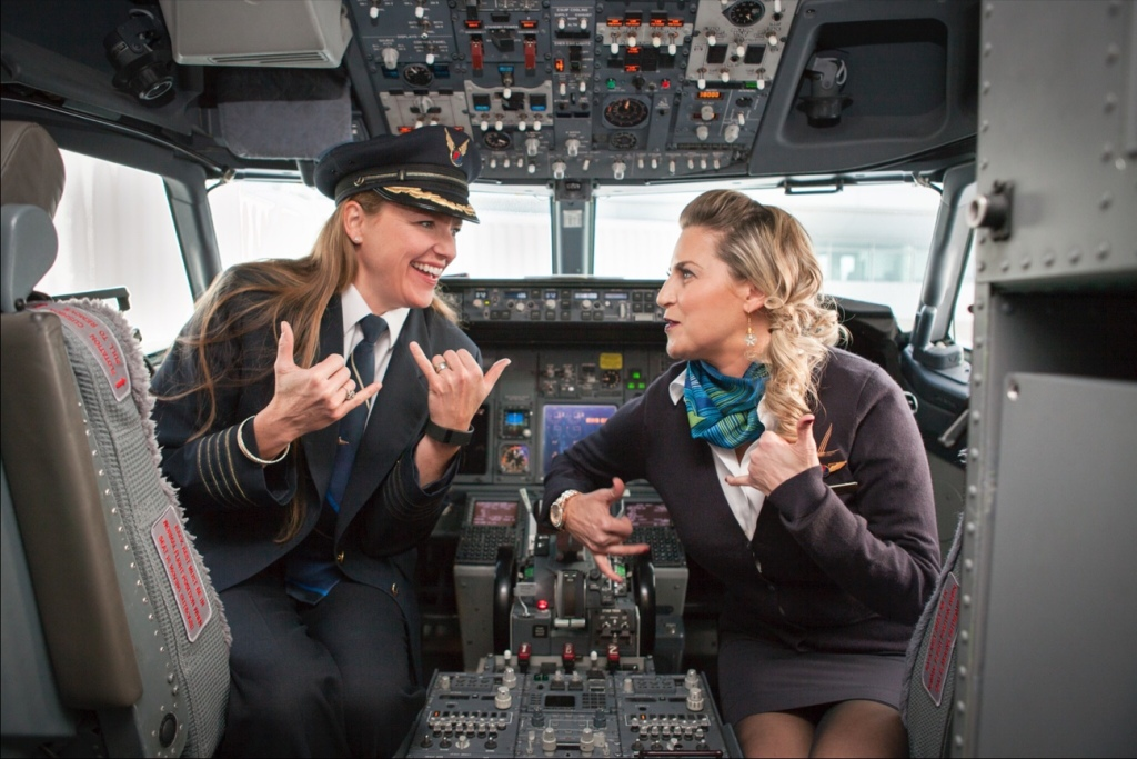 "This is a photo of Captain Jodi Harskamp sitting in the flight deck with Flight Attendant Jenny Stansel. The two are looking at each other and holding up a ""hang loose"" hand gesture."