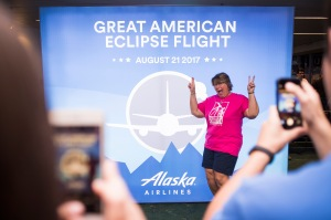 Kimberly Cassia stands in front of the Great American Eclipse Flight poster at the gate while onlookers snap photos.