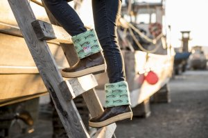 This is a closeup photo of a girl climbing up into a boat wearing Salmon Sisters branded boots. The boots are brown with a blue salmon and hook design.