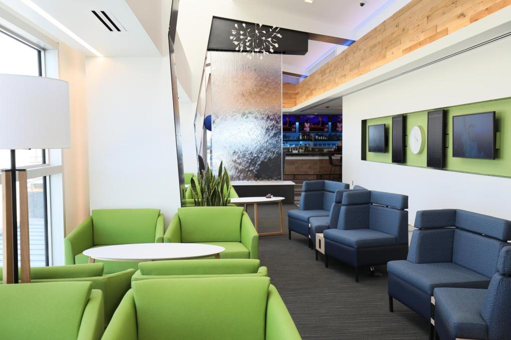 This is a photo of the new Alaska Lounge with green and navy seats, flatscreen TVs and a glass wall.