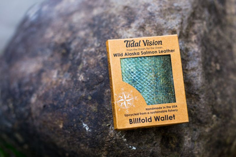 This is a photo of a packaged Tidal Vision Alaska Salmon Leather wallet sitting on a beach rock.