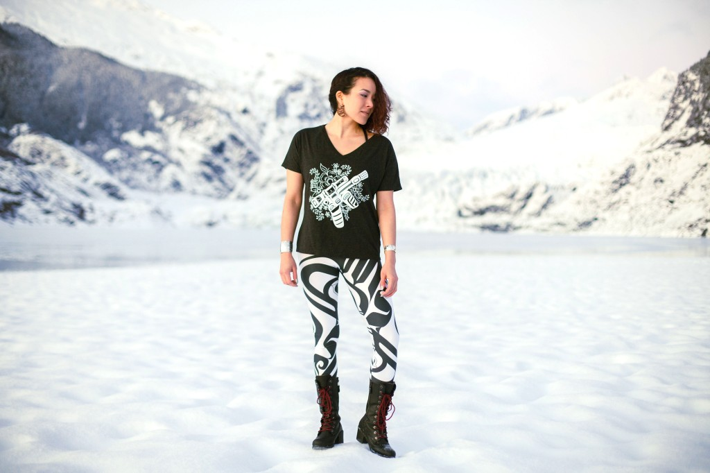 This is a photo of a woman standing on a snowy beach in front of a glacier wearing a t-shirt and leggings featuring contemporary Alaska Native artwork by Trickster Co.