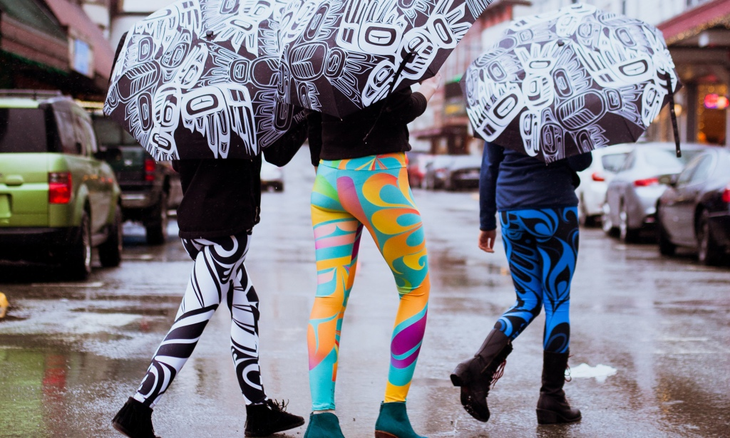 This is a photo of three women walking on a rainy street in bright leggings and umbrellas featuring contemporary Alaska Native artwork by Trickster Co.