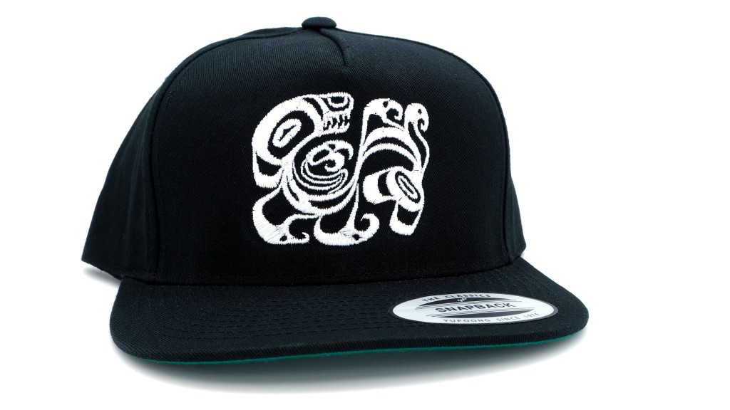 This is a photo of a black men's snap back style hat featuring a white Alaska Native contemporary design by Trickster Co.