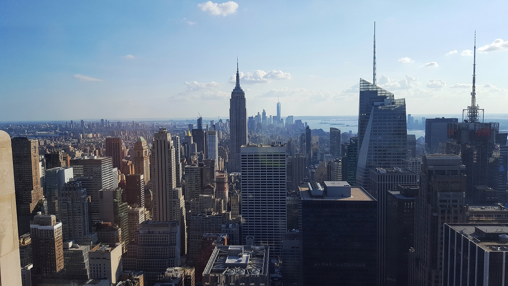 View looking south from a top-floor building in Manhattan, with the skyline, including the Empire State Building, in the distance.