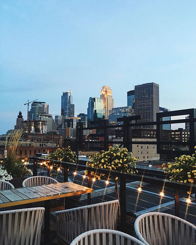 This is a photo of a rooftop cocktail bar overlooking the Minneapolis skyline in the evening light.