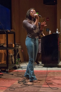 This is a photo of a young woman singing on a practice stage.