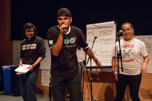 This is a photo of a group of three students rapping on a practice stage.