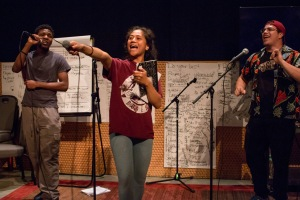 This is a photo of three students on a practice stage singing/rapping. The student in the middle is holding her microphone to the audience asking them to sing along.