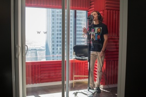 This is a photo of a student in the W Seattle Sound Suite. He is recording vocals.