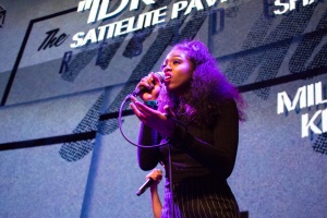 This is a photo of a student singing on stage at the Residency's hip hop showcase.